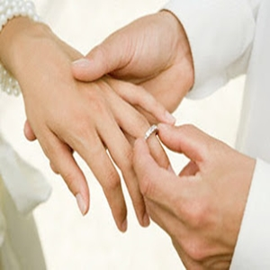 Man placing wedding ring on brides finger --- Image by © Image Source/Corbis