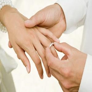 Man placing wedding ring on brides finger --- Image by © Image Source/Corbis
